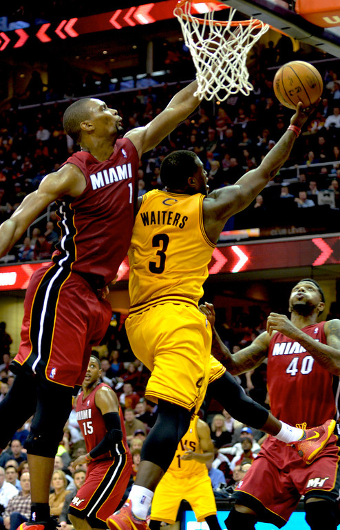 . Jeff Forman/JForman@News-Herald.com Chris Bosh blocks a shot by Dion Waiters in the second half of the Cavaliers\' 100-96 loss to the Heat March 18 at Quicken Loans Arena.
