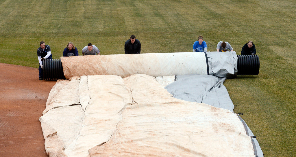 . Maribeth Joeright/MJoeright@News-Herald.com<p> The grounds crew rolls up the tarp in preparation of the Lake County Captains home opener, April 4, 2014.