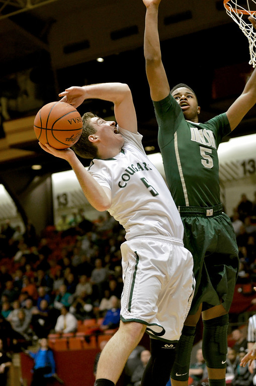 . Jeff Forman/JForman@News-Herald.comv Ben Meola shoots as St. Vincent St. Mary\'s Josh Williams defends in the first quarter of Lake Catholic\'s Division II regional semifinal game March 13 against the Fighting Irish March 13 at the Canton Civic Center.