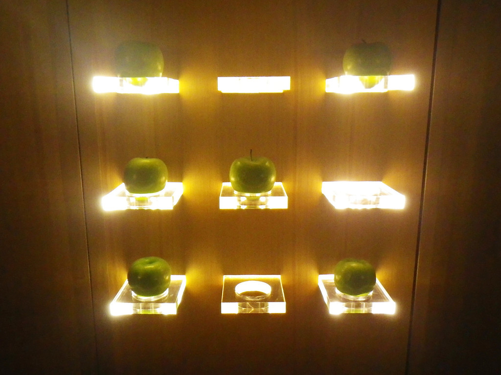 . Janet Podolak/JPodolak@News-Herald.comFresh Granny Smith apples are replenished as guests help themselves from a modern- looking  rack lit like artwork from below.
