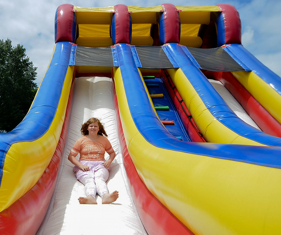 . Eric Bonzar/EBonzar@morningjournal.com<p> Emese Toth, 12, takes a turn on an inflatable slide during the Camp I.D.E.A.S. carnival July 16.