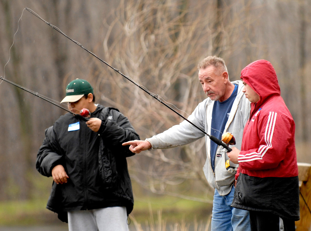 . Jeff Forman/JForman@News-Herald.com Rick Kimford helps his son Joseph Desoto during the Lake Metroparks Fantastic Fishing program for people with disabilities April 30 at Hidden Lake in Leroy Township. They live in Madison Township. At left is Marcus Manzi, of Willoughby.