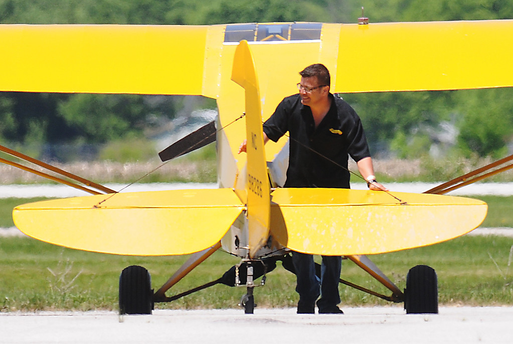 . Jim Bobel/JBobel@MorningJournal.com Emerson Stewart pushes his Piper J3 Cub back into postion on the flight line after performing at the  Discover Aviation Air Show at the Lorain County Regional Airport.