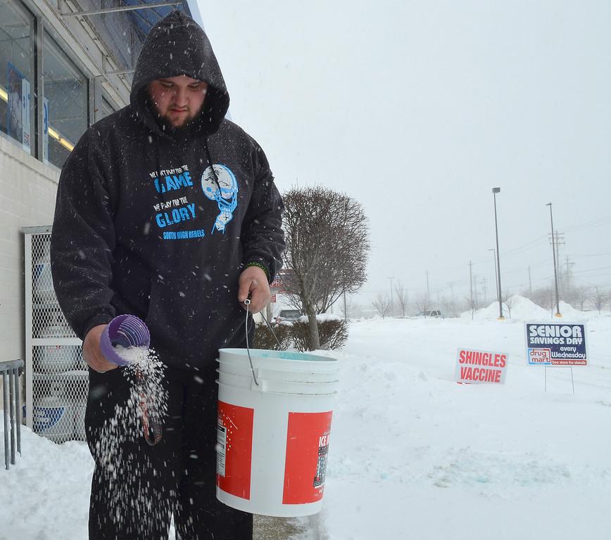 . Michael Allen Blair/MBlair@News-Herald.com Travis Patrick of Eastlake puts salt down on the walkway Wednesday at Discount Drug Mart in Eastlake.