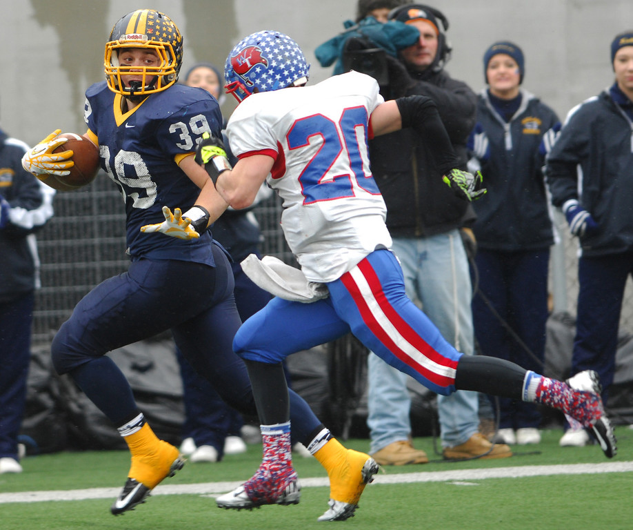 . Michael Allen Blair/ MBlair@News-Herald.com Kirtland runningback Adam Hess runs down the sideline as he stiff arms Wayne Trace linebacker Tyler Showalter during the first quarter of Friday\'s Div VI state championship victory over Wayne Trace at Fawcett Stadium in Canton.