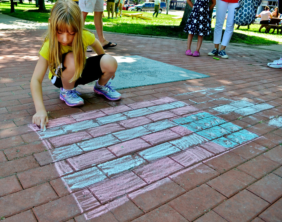 . Jeff Forman/JForman@News-Herald.com Mary Adamic, 11, uses chalk to draw an American Flag on Chardon Square during the July 4th Old Glory Day celebration. Mary was at the event with her mother, Teresa Adamic. They live in Huntsburg.