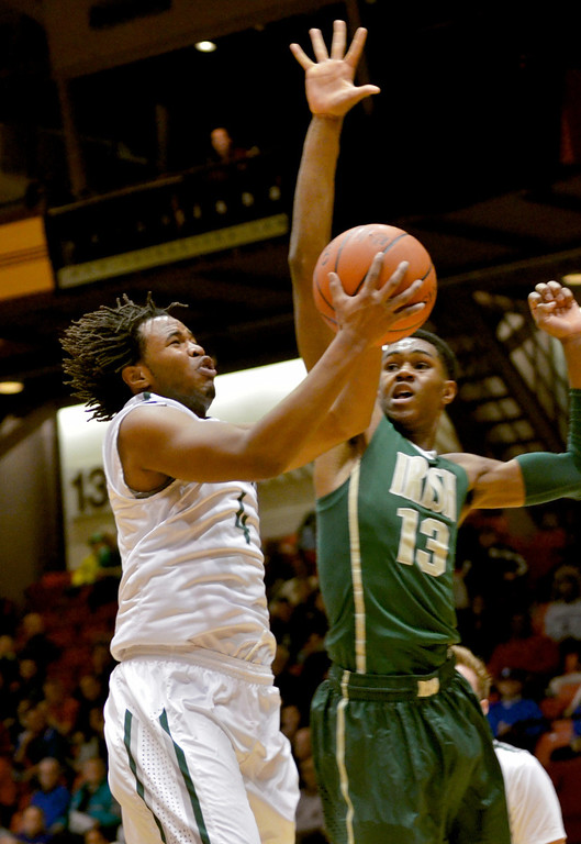 . Jeff Forman/JForman@News-Herald.com Kareem Haddix goes up against St. Vincent St. Mary\'s VJ King in the first half of Lake Catholic\'s Division II regional semifinal game March 13 against the Fighting Irish March 13 at the Canton Civic Center.