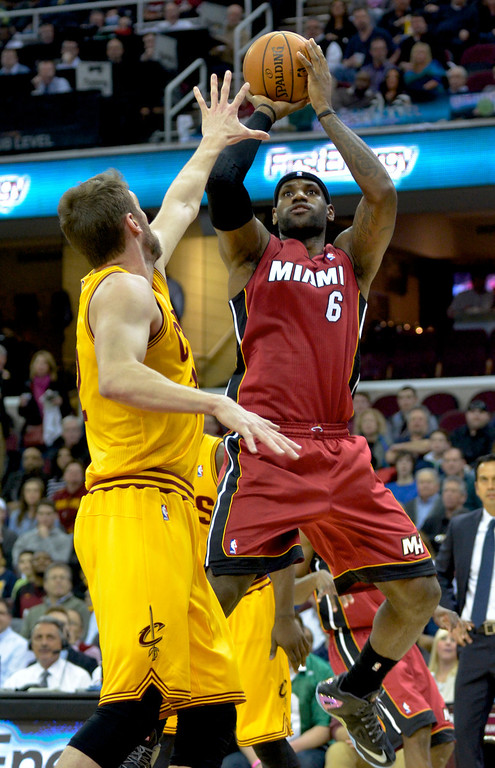 . Jeff Forman/JForman@News-Herald.com LeBron James shoots over Spencer Hawes during the firts quarter of the Cavs\' game against the Heat March 18 at Quicken Loans Arena.