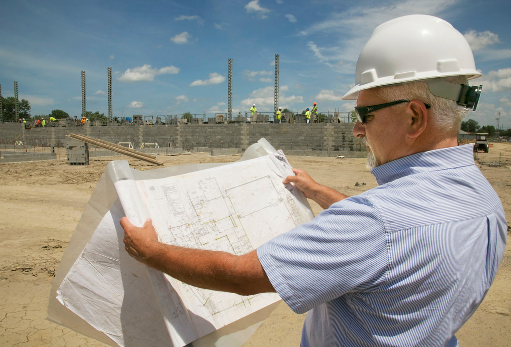 . Michael Allen Blair/MBlair@MorningJournal.com Jeff Hawks, executive director of operations for Lorain City Schools looks over a blueprint of what will be the gymnasium of the new Lorain Admiral King High School in Lorain on June 30.